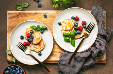 Pancakes with summer berries served for breakfast, overhead view on a table setting