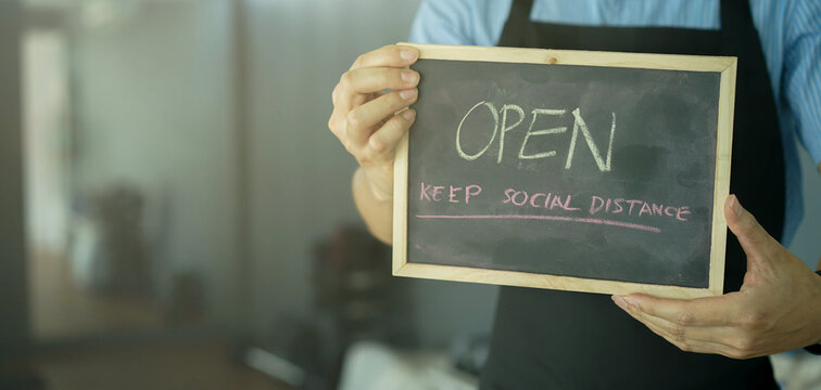 close up young business owner man holding chalkboard with message open to promote and inform reopening after lock down due to coronavirus pandemic for business and startup concept