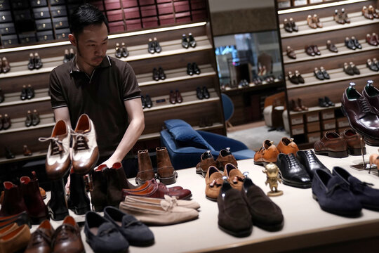 Shop's manager sorts handmade leather shoes at the Medallion store, following the coronavirus disease (COVID-19) outbreak, inside a shopping mall in Beijing