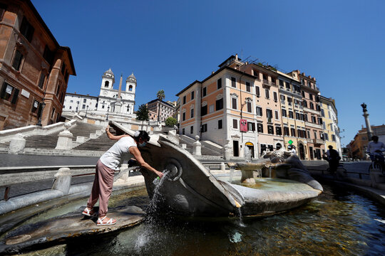 A woman fills a bottle of water in a fountain at the Spanish Steps during hot weather in Rome