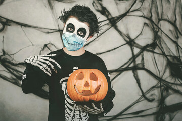 Happy Halloween.kid wearing medical mask in a skeleton costume with halloween pumpkin