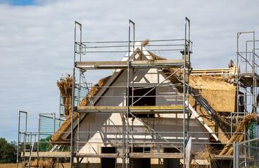 Das Dach eines Rohbaus wird mit Reet gedeckt
