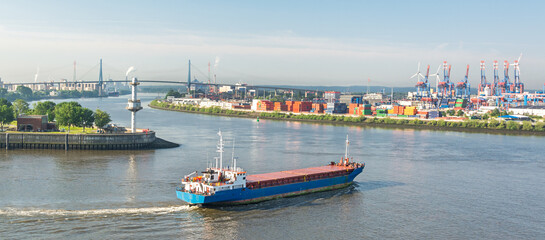 Panorama shot of container vessel steering towards the harbour and container terminal at the Elbe river in Hamburg