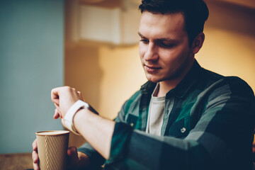 Young male looking at smartwatch touchscreen get notification about new message holding coffee cup, hipster guy using wearable computer apps for communication watching display settings on break