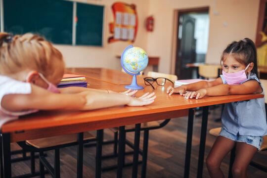 Two schoolgirls in medical masks are sitting at a school desk, opposite each other, group session, back to school, teaching children, social distance during epidemic