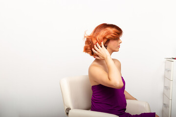 Wall Murals kids room Beautiful redhead woman sitting in chair and adjusting her messy hair in front of mirror.