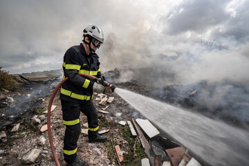 Side view of brave fireman in protective uniform standing with hose and extinguishing fire on dump in mountains