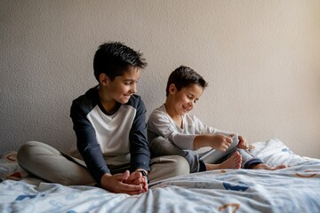 Smiling brothers in sleepwear sitting on cozy bed and watching movie together while entertaining at home