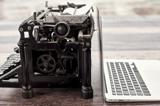 Modern netbook and old fashioned typewriter placed on wooden table on terrace