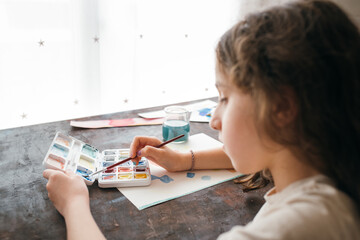 From above of anonymous skilled little girl painter sitting at table and creating pictures on paper with paintbrush and aquarelle