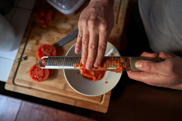 Stock photo of an aerial view of hands of a man grating tomato on top of a piece of wood in a kitchen