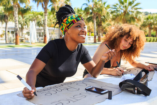 Diverse female activists making placards with black lives matter and no justice no peace inscriptions while preparing for strike against racism
