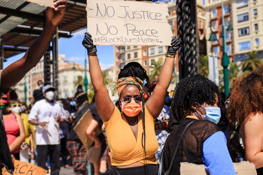 African American female in medical mask and gloves standing in city with poster with inscription no justice no peace and black lives matter surrounded by people