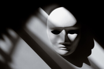 Emotionless plastic mask placed in room with sunbeam on white background