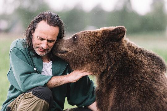 An adult man and a bear hug.