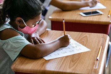 Girl with face mask working on math sheet in classroom