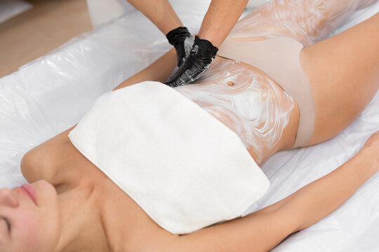 Cosmetologist applies a moisturizing mask on the body of a young girl in a cosmetology clinic before the wrapping procedure. Body Care. Spa Treatment.