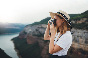Wall Mural - activ young blonde girl in summer hat takes photo on retro camera of panorama horizin mountain landscape walking on trip outdoors, hipster tourist enjoys hobby of photographing nature spain on holiday