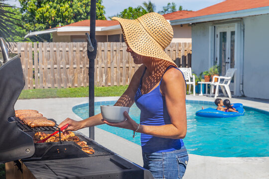 Summertime is about being outdoors at home by the pool grilling. The mother grills some sausage and bastes the chicken with barbecue sauce while the kids play in the pool.