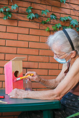 elderly woman with face mask painting a birdhouse
