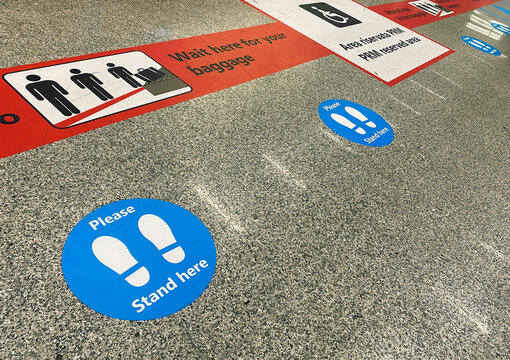 Stickers on the floor near the baggage claim belt at the airport that warn of keeping social distance during the health emergency during the coronavirus pandemic