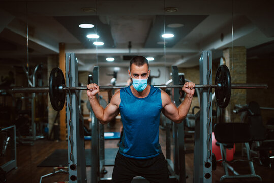 A young caucasian athlete man with a mask on his face exercises and lifts weights in the gym. COVID 19 coronavirus protection