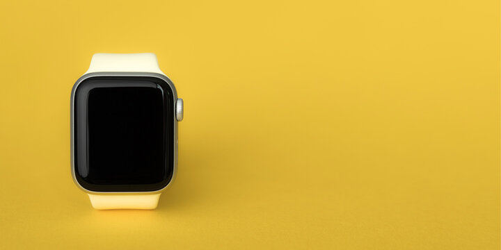 Petrozavodsk, Russia - July 12, 2020: Close-up new Apple Watch Series 4 aluminum and ceramic case. On yellow background.