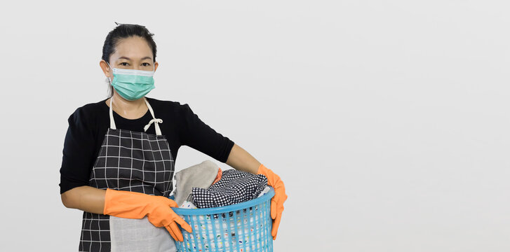 Asian Woman in a housekeeper looks wearing apron cleaning