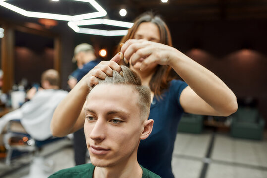 Working process. Professional barber girl or female hairdresser serving client in Barbershop, styling hair of young man with gel or wax