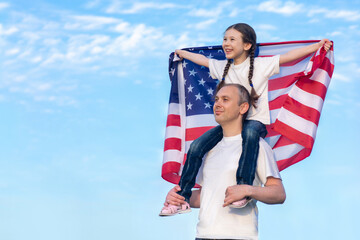 Happy daughter sits on her father's shoulders and holds the American flag above her head. American...