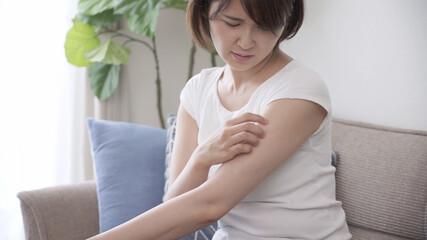 腕を掻いている若い女性