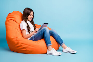 Portrait of nice attractive cheerful cheery focused wavy-haired girl sitting in chair using tablet ebook isolated on bright vivid shine vibrant blue teal turquoise color background