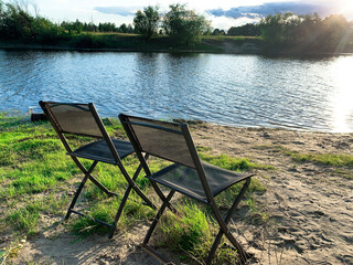 Beach chairs by the river. Evening sunset, sunshine. Natural landscape, river bank at sunset....