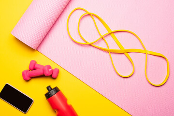 top view of resistance band on pink fitness mat near smartphone, sports bottle, dumbbells on yellow...