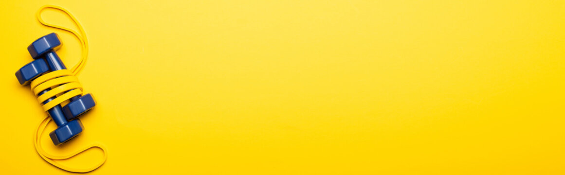 top view of blue dumbbells in resistance band on yellow background, panoramic shot