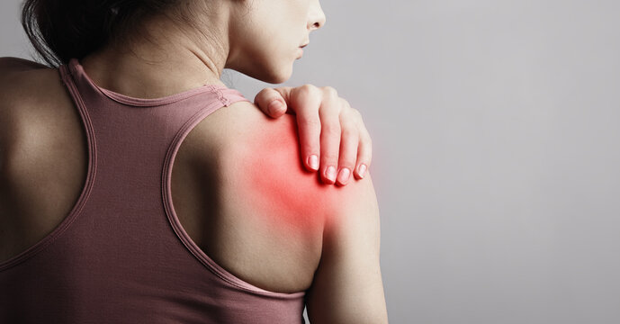 Young strong sporty woman suffering from pain in shoulder in sport wear. Touching the hand. Sports exercising injury. Closeup portrait with highlighted in red and empty space. Back view. The concept
