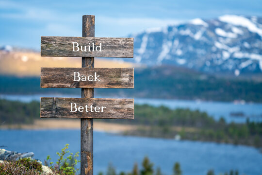 Build back better text on wooden signpost outdoors in landscape scenery during blue hour. Sunset light, lake and snow capped mountains in the back.