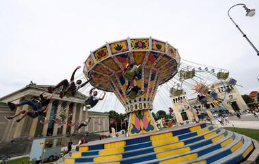 People ride on a merry-go-round on the Koenigssplatz square in Munich