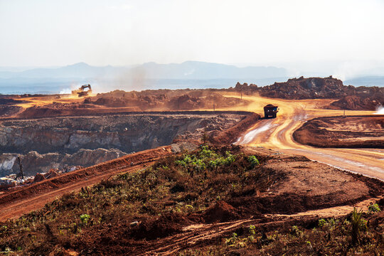 Open pit mine in Madgascar, with huge crane and trucks ro bring ore to a processing plant