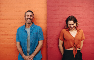 Couple standing by multicolored wall