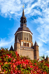 St. Nicholas Church with glowing autumn plants in the foreground in the old town of Stralsund, Germany