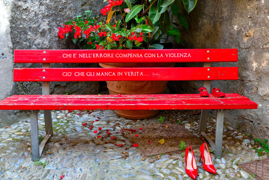 red bench with shoes symbol against violence against women cervo italy     I translate written in Italian: those who make mistakes make up for violence: what they really lack ... (Gothe)