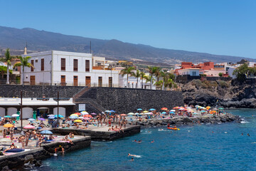 Lots of residents sunbathing and swimming in the small harbor in Alcala in a hot sunny summer day after the strict lockdown finished at Puerto de Alcala, Tenerife, Canary Islands, Spain