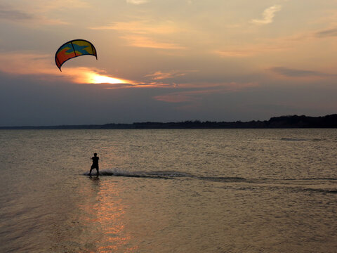 Windsurfing at Sunset on calm water.