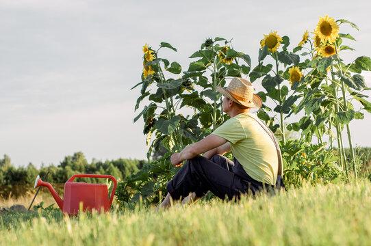 Portrait of bearded man with straw hat relaxing in garden