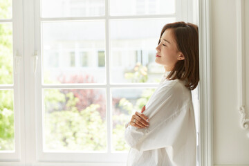 serene young asian woman staying at home leaning against window frame