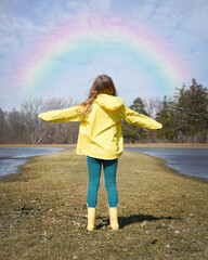 Girl Outside in Raincoat Looking at Rainbow in Sky