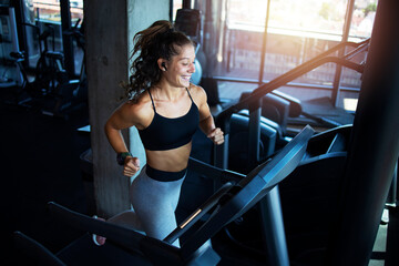 Top view of smiling woman exercising and training in the gym on treadmill running machine. Healthy lifestyle and positive people.