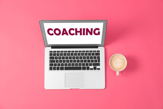 Business training or life coaching. Modern laptop and cup of coffee on pink background, flat lay