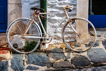Old rusty white Bicycle lean at the Wall, Cadaques, Spain